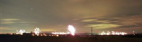 Das Bild zeigt entfernte Dörfer, in denen Feuerwerk abgebrandt wird. Im Hintergrund sieht man den Asse-Höhenzug und Windräder, vor den Dörfern ist eine Hochspannungs-Freileitung