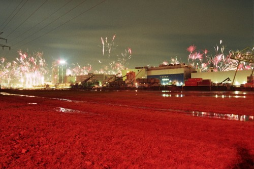 Das Bild zeigt Feuerwerk über einem Industriegelände. Der Boden ist rot eingefärbt.