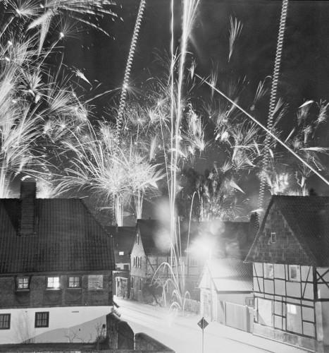 Das s/w-Foto zeigt Feuerwerk über Häusern, sehr viel Feuerwerk.