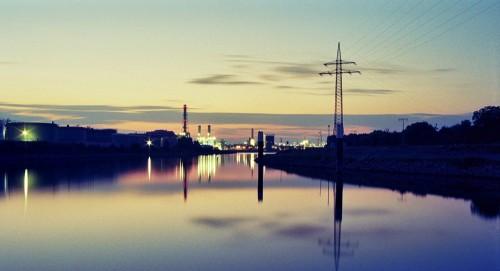 Das Bild zeigt an Industriegebiet am späten abend, es führt der Neckar vom Fotografen weg. Man sieht Schornsteine, Lichter und auf der rechten Seite eine Hochspannungs-Freileitung