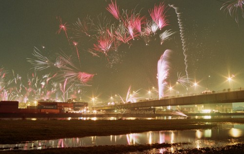 Das Bild zeigt Feuerwerk über einer Brücke und Hafengelände, wo Container stehen.