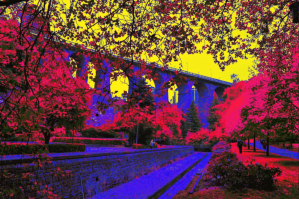Das BIld zeigt eine Landschaft mit einer Straße auf einer Bogenbrücke, die Farben sind unnatürlich Verfremdet, die Blätter Rot, der Himmel Gelb, die Steine Blau