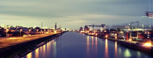 Das Bild zeigt einen Binnenhafen bei Nacht, rechts ist die Containerabfertigung, in der Mitte ein Kanal, Links Industriegebiete, es gibt viele Lichter und die Kräne haben aufgrund der langen Belichtungszeit spuren hinterlassen