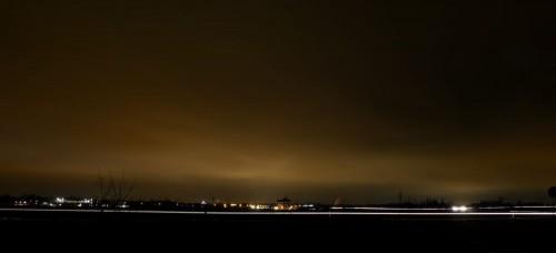 Das Foto ist eine nächtliche Landschaftsaufnahme, man sieht weiter hinten ie hellen Lichter der Stadt Braunschweig und das die Wolken von der Stadt aus angeleuchtet werden. Entlang der Straßen sind die Lichter der Autos weiße Streifen