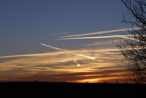 Das Foto zeigt den Sonnenuntergang, die Sonne ist fast ganz weg, man sieht Kondensstreifen