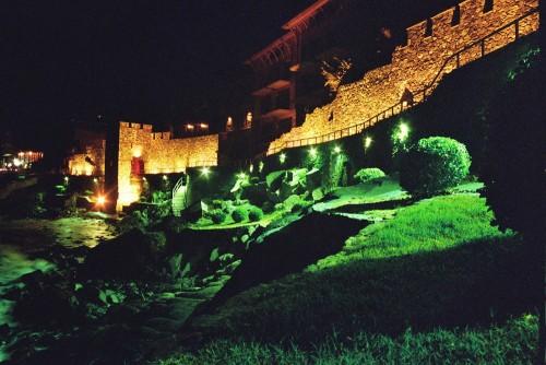 Das Foto zeigt die gelb und grün ausgeleuchtete Stadtmauer von Sozopol und den Fußgängerweg an der Mauer