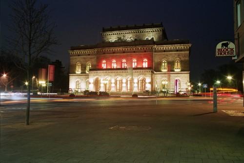 Das Bild zeigt das Theatergebäude bei Nacht, auf dem Theaterkreisel sieht man LIchtspuren der Autos