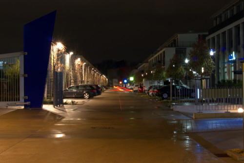 Das Bild zeigt eine Straße bei Nacht, rechts und Links parken Autos zwischen den Bäumen, man sieht die Rücklichter von einem Auto, auf beiden Seiten sind laternen, rechts stehen moderne Häuser