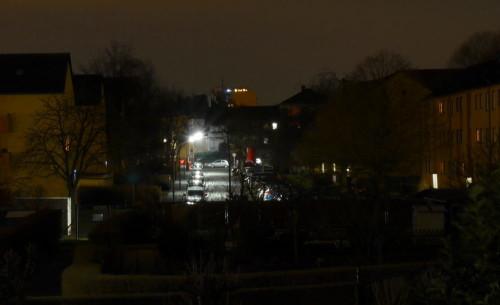Das Bild zeigt die Nachtaufnahme einer Wohnstraße, rechts und links der Straße stehen gebe Mehrfamilienhäuser