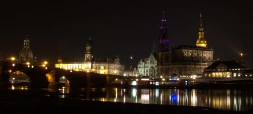 Das Bild zeigt historische Gebäude in der Altstadt von Dresden von der anderen Elbseite (Neustadt) aus. Man sieht auch den Theaterkahn und eine Elbbrücke mit Bogenmauerwerk