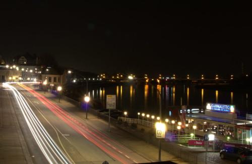 """Das Bild zeigt eine nächtliche Straßenszene in der Altstadt von Dresden, neben der Elbe. Man sieht die Spuren der Autscheinwerfer, die Straße ist Links, rechts die Elbe und auf der Elbe das Restaurant """"Kahnaletto"""""""