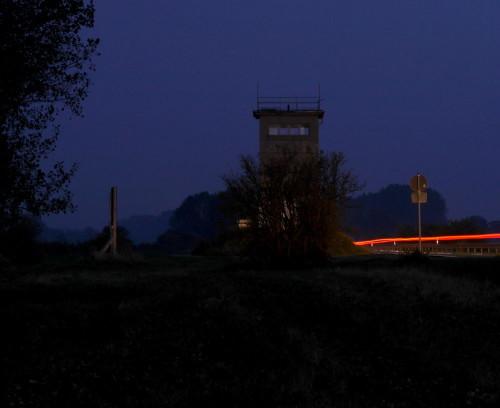 """Das Bild zeigt den Beton-Grenzturm in Mattierzoll bei Nacht (von der """"West-Seite""""). Rechts vom Turm ist eine Straße, auf der sieht man die Rücklichter von Autos als Spuren, Links neben dem Turm ist ein Großes Baustellen-Schild, von dem man aber nur die Seite sieht."""
