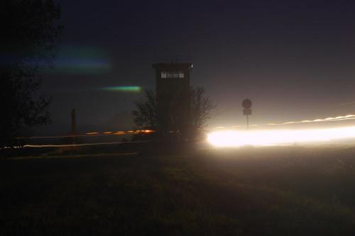 """Das Bild zeigt den Beton-Grenzturm in Mattierzoll bei Nacht (von der """"West-Seite""""). Rechts vom Turm ist eine Straße, auf der sieht man die Schwinwerfer der Autos als Spuren, Links neben dem Turm ist ein Großes Baustellen-Schild, von dem man aber nur die Seite sieht. Von rechts nach Links durch das Bild gehen dünne Lichtspurren von einem Traktor und man sieht Reflektionen von Lichtern im Nebel"""