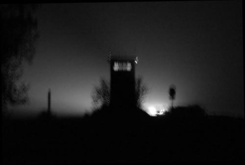 """Das Bild zeigt den Beton-Grenzturm in Mattierzoll bei Nacht (von der """"West-Seite""""). Rechts vom Turm ist eine Straße, auf der sieht man die Scheinwerfer der Autos. Das Bild ist in schwarz/weiß und verwackelt..."""