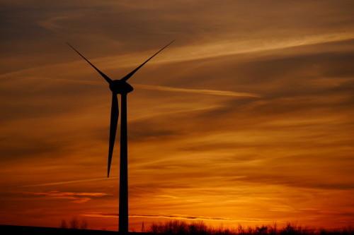 Das Bild zeigt die aufgehende Sonne hinter einem Windrad, die Sonne geht gerade auf und färbt die Wolken goldig ein. Das Windrad wird recht gross abgebildet.