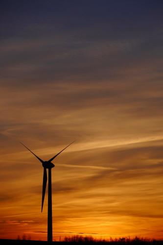Das Bild zeigt die aufgehende Sonne hinter einem stehenden Windrad. Die Sonne geht gerade auf und färbt die Wolken goldig ein.