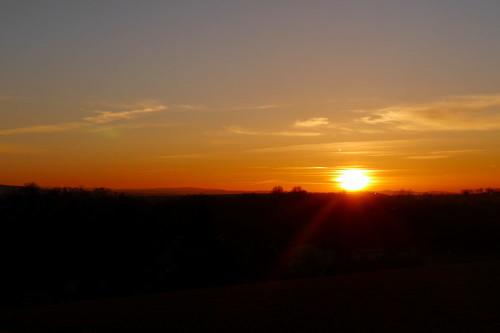 Das Bild zeigt einen Sonnenuntergang, die Sonne berührt gerade die Erde