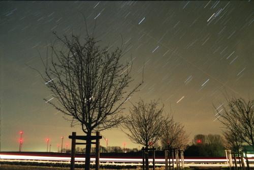 Das Bild zeigt den Nachthimmel, im Vordergrund sind ein paar Bäume und eine Straße, im Hintergrund Windkraftanlagen mit roten Positionslichtern. Die Sterne sind aufgrund der langen Belichtung Streifen