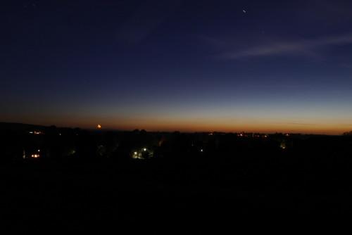 Das Foto zeigt eine Landschaft während der späten Dämmerung, man sieht ein paar Lichter an Häusern, der Himmel ist Dunkeblau und am Horizont Orange.