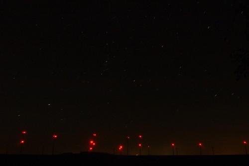 Man sieht dan Himmel, die Sterne bilden kurze Linien. Von den Windkraftanlagen sieht man die roten Positionslichter sehr deutlich.