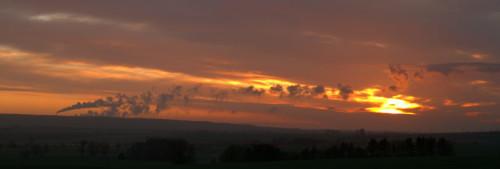 Das Bild zeigt einen Sonnenaufgang bei dichter Wolkendecke, im linken Bereich ist ein Schornstein eines Kraftwerks, der Rauch und der Rauch eines unsichtbaren Schornsteins gehen nach Rechts und sind teilweise vor der Sonne