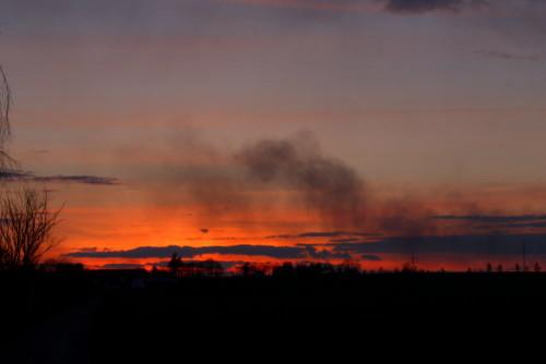 Kurz nach Sonnenuntergang, die Wolken glühen noch Orange, es ist Dunst in der Luft, Bäume usw. sind als Silouetten zu sehen.