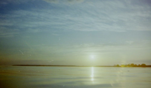 Das Bild zeigt die Sonne kurz vor Sonnenuntergang über einem ruhigen See, es ist eine Gegenlicht-Aufnahme.