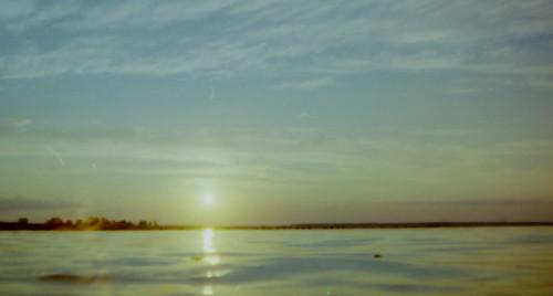 Das Bild zeigt die Sonne kurz vor Sonnenuntergang über einem ruhigen See, es ist eine Gegenlicht-Aufnahme. .