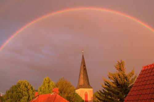 Auf dem Bild ist der Turm einer Kirche und Dächer. Über der Kirche ist ein Regenbogen.