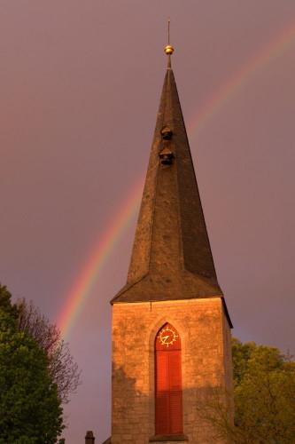 Das Bild zeigt den Kirchturm mit Uhr der Apostelkirche, hinter der Kirchturm geht ein Regenbogen durch den Himmel