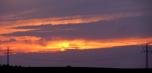 Das Bild zeigt einen Sonnenuntergang, die Sonne schaut nur durch einen kleinen Spalt zwischen den Wolken durch. Im Vordergrund sieht man ein Stück Freileitung mit zwei Masten