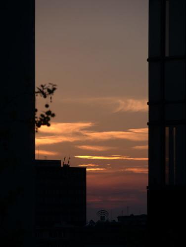Das zeigt einen Sonnenuntergang (oder besser die Reste davon, die Sonne selbst ist nicht zu sehen, nur orange-violett leuchtende Wolken) zwischen zwei Hochhäusern