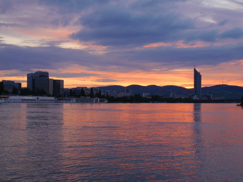 Das Bild zeigt den Sonnenuntergang an der Donau in Wien, auf dem Fluß sind Schiffe, im Hintergrund sieht man Berge und Häuser