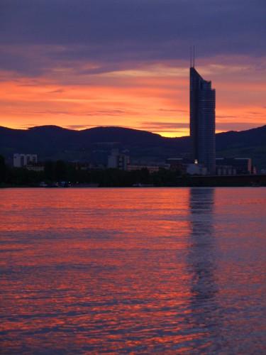 Das Bild zeigt einen Sonnenuntergang an der Donau, am Uferrand steht ein Hochhaus und weitere Häuser