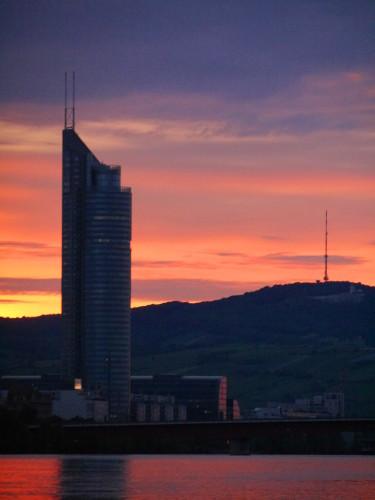 Das Bild zeigt ein Hochhaus (links), einen Mast auf einem Berg (rechts) und den Rest der untegehenden Sonne