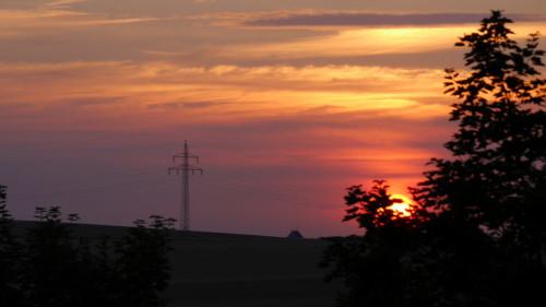 Das Bild zeigt einen Sonnenuntergang, die Sonne ist kurz vor dem Untergehen und hinter Bäumen verborgen auf der rechten Seite, im Linken drittel des Bildes steht ein Hochspannungsmast