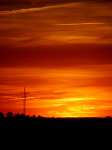 """Das Bild zeigt den Himmel beim bzw. kurz nach dem Sonnenuntergang. Der Himmel """"brennt"""" in Orange- und Rottönen. Auf der linken Seite sieht man einen Hochspannungsmasten."""