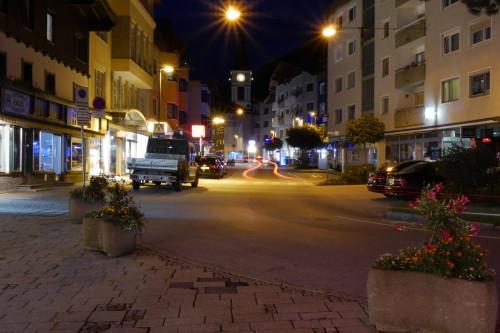 Das Bild zeigt die Bahnhofsstraße, eine Einkaufsstraße in Wörgl, bei Nacht. Die Lichter der Autos haben Spuren hinterlassen.. Im Hintergrund sieht man die Stadtkirche von Wörgl