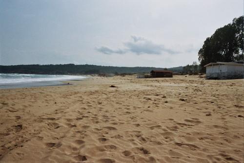 Das Bild zeigt einen leeren Sandstrand am Meer und vernagelte Hütten. Dazwischen sind Möwen.