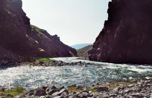Das Bild zeigt einen Fluss, der sich durch eine Schlucht zwischen Bergen/Hügeln schlängelt. Der Kamreastandort ist Dicht über dem Boden.