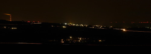 Das Bild zeigt eine NAchtaufnahme, man sieht die Stadt Schöningen, ein paar andere Dörfer, auf der linken Seite den Schornstein vom Kraftwerk Buschhaus und auf der rechten Seite Positionslichter von Windkraftanlagen.