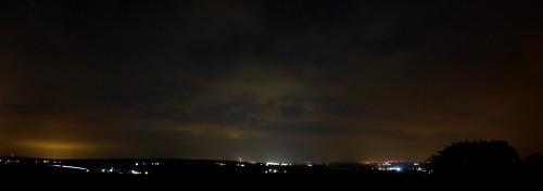 Das Bild zeigt eine Nachtaufnahme-Panoramaufnahme, man sieht die Stadt Schöningen, ein paar andere Dörfer, in der Mitte den Schornstein vom Kraftwerk Buschhaus und auf der rechten Seite Positionslichter von Windkraftanlagen.