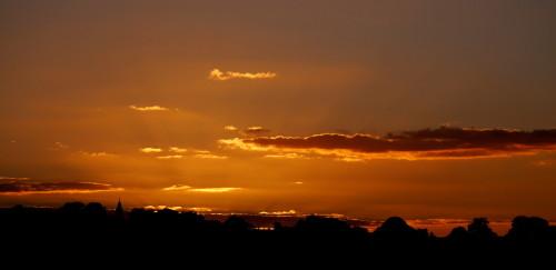 Das Bild zeigt eine Landschaft kurz nach Sonnenuntergang, der Himmel glüht noch goldig.