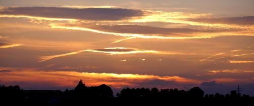 """Das Bild zeigt Wolken, die von der Sonne von """"Hinten"""" angestrahlt werden und blau/orange Leuchten"""