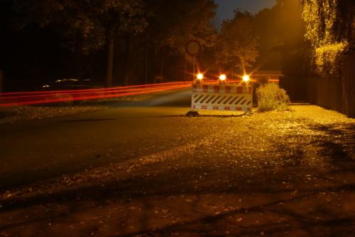 Das Bild zeigt eine Straße bei Nacht. Auf der Straße steht eine Absperrung zur Sperrung der Straße, man sieht die roten Rücklichter der Autos, die an der Absperrung vorbeigefahren sind.