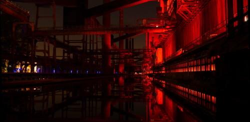 Das Bild ist in der alten Kokerei Zollverein aufgenommen, es zeigt die Industrieanlagen bei Nacht, die rot beleuchtet sind.