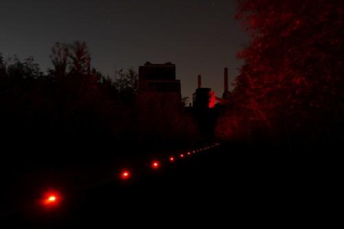 Das Bild zeigt die rot beleuchteten Gebäude und die roten Markierungsleuchten eines Fußweges in der Zeche Zollverein