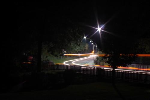 Das Foto zeigt die Hauptstraße in Winnigstedt, das Bild ist durch die Bäume aufgenommen. Man sieht die Streifen von Fahrzeuglichtern.