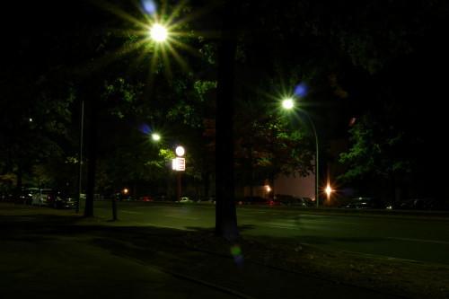 Das Bild zeigt eine nächtliche Straße in Berlin. Es ist eine Allee, rechts und LInks stehen Bäume und geparkte Atuos. Ziemlich in der Mitte steht eine Beleuchtete Uhr mit Werbetafeln.