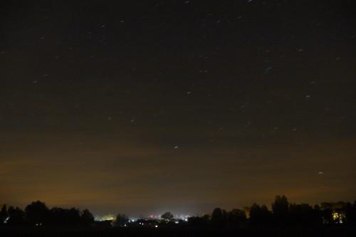Das Bild zeigt eine Nachtaufnahme von Winnigstedt, man sieht die roten Lichter der Windkraftanlagen, einige beleuchtete Fenster, viele Bäume und darüber den Himmel, an dem die Sterne schon streifen sind.